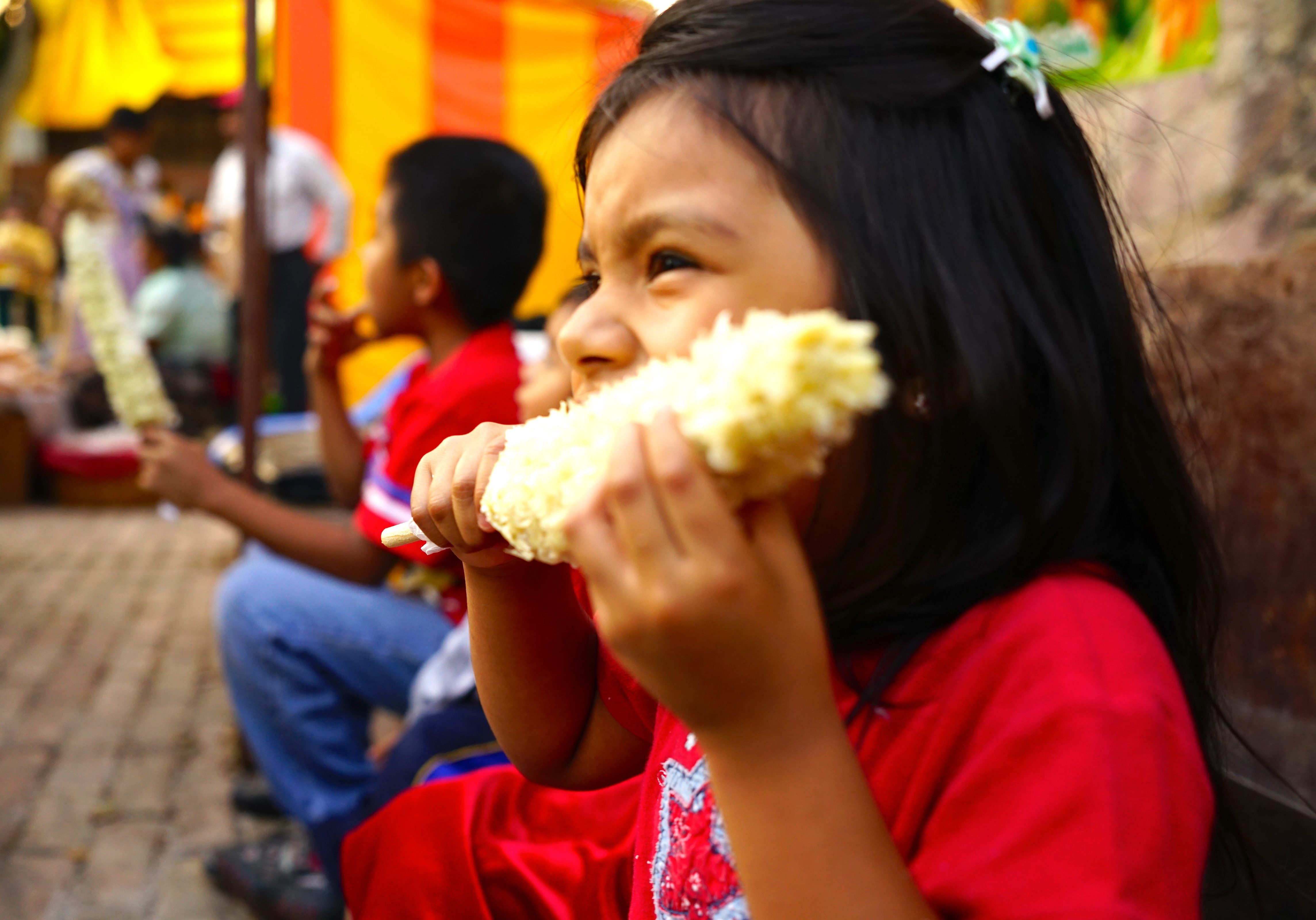 A girl eating elote